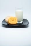橙色果酱卷蛋糕和曲奇饼结块与奶油色装填并且使牛奶痛苦 免版税图库摄影
