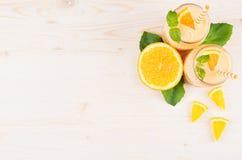 橙色柑橘圆滑的人装饰边界在玻璃瓶子的有秸杆的,薄荷的叶子,裁减桔子,顶视图 免版税库存照片