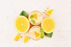 橙色柑橘圆滑的人装饰边界在玻璃瓶子的有秸杆的,薄荷的叶子,裁减桔子,顶视图 免版税库存图片