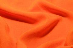 橙色棉纺织品工厂织品纹理挥动并且折叠背景 免版税库存照片
