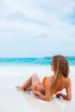 橙色比基尼泳装的妇女在一个热带海滩 免版税库存图片