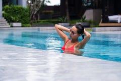 橙色比基尼泳装的Tenned美丽的亚裔坐在游泳池的妇女和sunlasses 时兴的纵向 典雅 库存照片