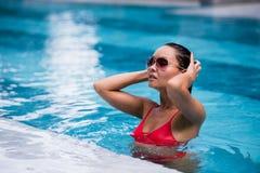 橙色比基尼泳装的Tenned美丽的亚裔坐在游泳池的妇女和sunlasses 时兴的纵向 典雅 库存图片