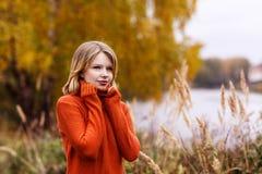 橙色毛线衣的美丽的女孩 库存照片