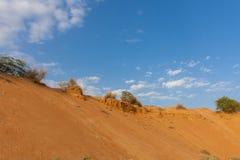 橙色沙丘和一明亮的天空蔚蓝与云彩 库存照片