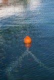 橙色浮体在蓝色海洋水中 免版税图库摄影