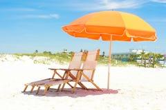 橙色海滩睡椅和风雨棚 免版税库存照片