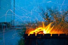 橙色火引起在蓝天背景房子的金属火盆海滨的 免版税库存照片