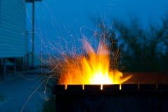 橙色火引起在蓝天背景房子的金属火盆海滨的 免版税库存图片
