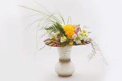 橙色玫瑰、金丝桃属植物和蕨的花卉构成 在一个透明玻璃花瓶的花的布置 查出在白色 库存照片