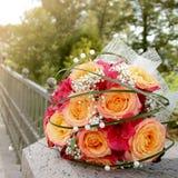 橙色玫瑰和红色兰花花束装饰了白色小珠 库存图片