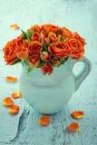 橙色玫瑰花束在一个蓝色花瓶的 图库摄影