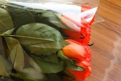 橙色玫瑰花束在一张木桌上的与反射 免版税库存图片