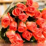 橙色玫瑰花束在一张木桌上的与反射 免版税库存照片