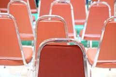橙色现代椅子行在有被弄脏的绿色地板的展览馆 库存图片