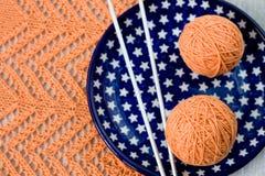 橙色球、被编织的样式和nedles 库存照片
