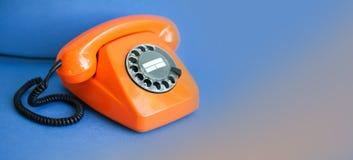 橙色电话蓝色背景 减速火箭的样式塑料手机接收器通信电话中心概念 浅深度 库存照片