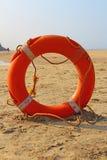 橙色白色lifebuoy在沙子 免版税库存图片