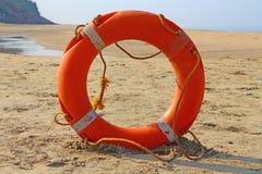 橙色白色lifebuoy在沙子 免版税库存照片