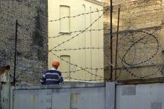 橙色盔甲的人在铁丝网后的工地工作 免版税库存照片
