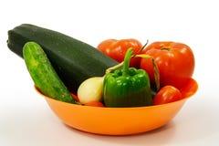 橙色碗在白色背景的庭院新鲜蔬菜 免版税库存图片