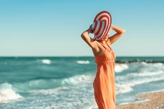 橙色礼服的妇女在海海滩 库存图片