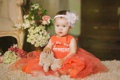 橙色礼服的孩子有一张严肃的面孔的 库存图片