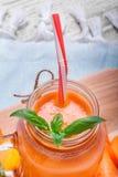 橙色红萝卜圆滑的人的特写镜头在一个金属螺盖玻璃瓶的有薄菏傻的绿色叶子的在光的弄脏了背景 库存照片