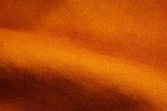 橙色织品背景的纹理 库存图片