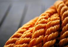 橙色结辨的尼龙绳索在被缠结的卷黑色背景中 库存图片