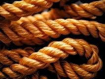 橙色结辨的尼龙绳索在被缠结的卷黑色背景中 免版税库存图片