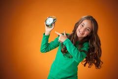 橙色背景的逗人喜爱的快乐的小女孩 库存图片