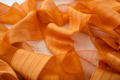 橙色背景豪华布料或难看的东西丝绸纹理缎波浪折叠  库存图片