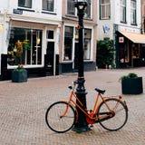 橙色自行车在一个安静的镇 免版税库存照片