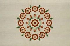 橙色花的圆的装饰品刺绣在扭转的词根的与在棉织物的叶子 库存图片