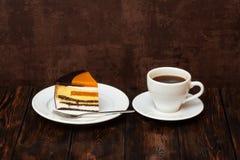 橙色蛋糕切片和咖啡杯在木背景 免版税图库摄影