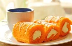 橙色蛋糕卷被充塞的奶油吃加上在盘的咖啡 库存照片