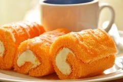 橙色蛋糕卷被充塞的奶油吃加上在盘的咖啡 免版税库存图片