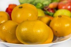 橙色蜜桔特写镜头到一个盘里,在几棵菜前面 免版税库存图片