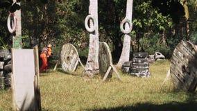 橙色衣服的人与打在迷彩漆弹运动领域的枪和防毒面具迷彩漆弹运动比赛与轮胎和木避难所 影视素材