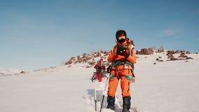 橙色衣服的女孩登山人站立与有一张地图的一种电子片剂在他的手上并且检查路线 ? 股票视频
