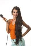橙色衬衣的可爱的妇女有话筒的 免版税库存照片