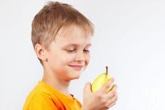 橙色衬衣的小滑稽的男孩用黄色水多的梨 库存照片