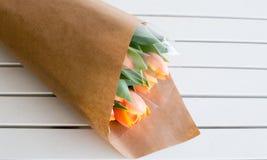 橙色郁金香被包裹的花束在桌上的 库存图片