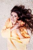 橙色长袍的美丽的妇女有美丽的深色的头发的 图库摄影