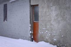 橙色门在一多雪的天 库存图片