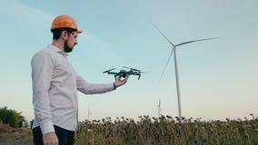 橙色防护盔甲的白种人工程师投入风镜并且发射从他的手的一条聪明的quadrocopter寄生虫 股票录像