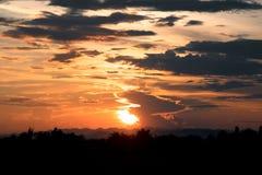 橙色阳光看法和黑暗的云彩和山在晚上时间 免版税图库摄影