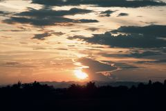 橙色阳光看法和黑暗的云彩和山在晚上时间 免版税库存图片
