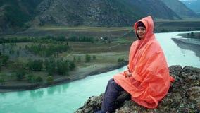 橙色雨衣的女孩坐山的上面由Katun河 美好的横向 股票视频